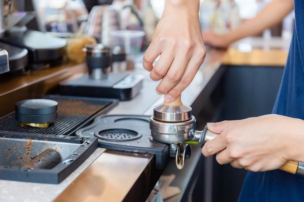 Schließen sie oben von barista hand, die kaffee auf der maschine macht