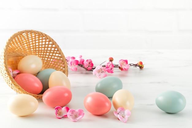 Schließen sie oben von bunten ostereiern im korb mit rosa pflaumenblume auf hellweißem holztischhintergrund.