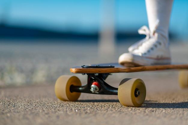 Schließen sie oben von damenbein in den weißen turnschuhen, die nach extremer lustiger fahrt ihr hölzernes longboard skateboard stillstehen. modernes städtisches hippie-mädchen haben spaß. guten sonnigen sommertag zum skateboarden und spaß haben