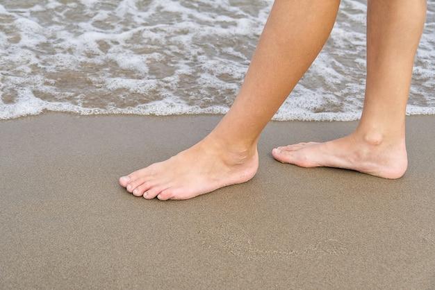 Schließen sie oben von den beinen des kindes, die auf sandküste und meerwasser gehen