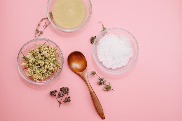 Schließen sie oben von den bestandteilen der ayurvedischen behandlung oder der gesichtsmaske. gelber lehm, gelbwurzpulver und getrocknete kamille, seegrobes salz in den glasschalen auf einer rosa pastellfarboberfläche. flachgelegtes blog