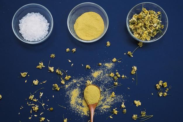Schließen sie oben von den bestandteilen der ayurvedischen behandlung oder der gesichtsmaske. gelber lehm, kurkumapulver und getrocknete kamille, seegrobes salz in glasschalen auf einer klassischen blauen farbtrendoberfläche. flach liegen