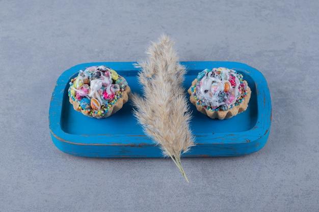 Schließen sie oben von den bunten hausgemachten keksen auf blauem holzbrett