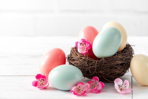 Schließen sie oben von den bunten ostereiern im nest mit rosa pflaumenblume auf hellweißem holztischhintergrund.