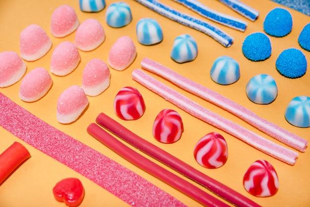 Schließen sie oben von den bunten süßen zuckersüßigkeiten in einer reihe