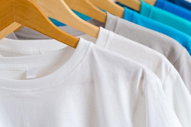 Schließen sie oben von den bunten t-shirts auf aufhängern, kleiderhintergrund