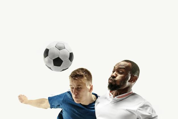 Schließen sie oben von den emotionalen männern, die fußball spielen, die den ball mit dem kopf auf lokalisiert auf weißer wand schlagen. fußball, sport, gesichtsausdruck, menschliches gefühlskonzept. copyspace. kämpfe um das ziel.