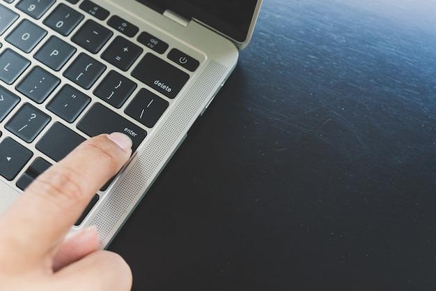 Schließen sie oben von den fingern der rechten hand von den asiatischen männern, die beschließen, enter-taste für laptop zu drücken