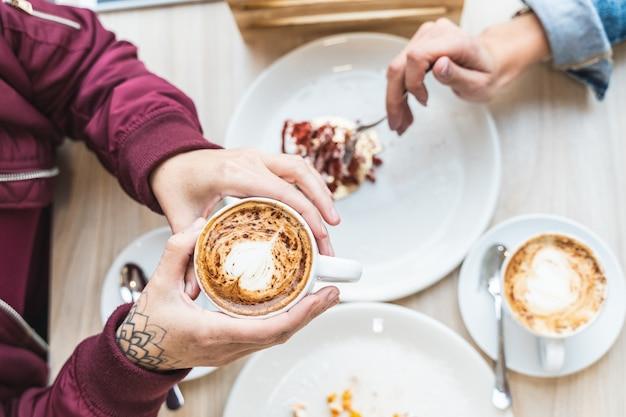 Schließen sie oben von den frauen-händen, die einen heißen cappuccino in einem café halten.