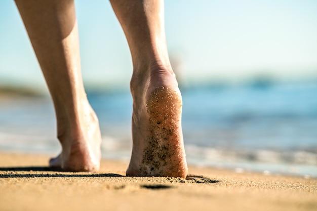 Schließen sie oben von den frauenfüßen, die barfuß auf sand gehen und fußabdrücke auf goldenem strand hinterlassen. konzept für urlaub, reisen und freiheit. menschen, die sich im sommer entspannen.