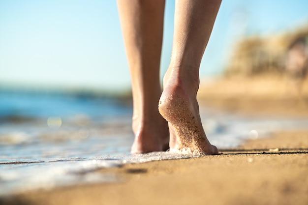 Schließen sie oben von den frauenfüßen, die barfuß auf sandstrand im meerwasser gehen. konzept für urlaub, reisen und freiheit. menschen, die sich im sommer entspannen.