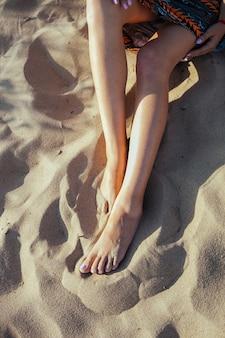 Schließen sie oben von den frauenfüßen, die barfuß auf sandstrand sitzen. konzept für urlaub, reisen und freiheit. menschen, die sich im sommer entspannen.
