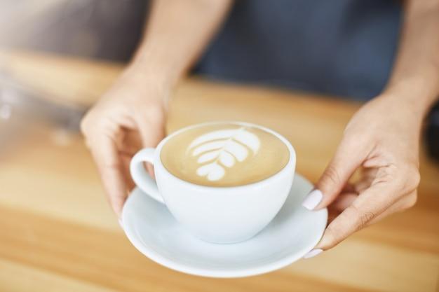 Schließen sie oben von den frauenhänden, die einen cappuccino in einer tasse mit latte art dienen. barista-konzept.