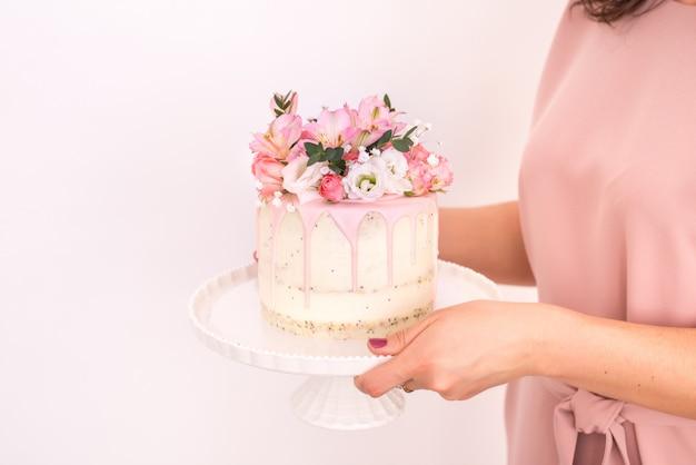 Schließen sie oben von den frauenhänden, die einen kuchen halten, der mit blumen auf einem weißen hintergrund verziert ist