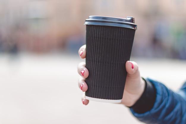 Schließen sie oben von den frauenhänden, die papiertasse kaffee halten