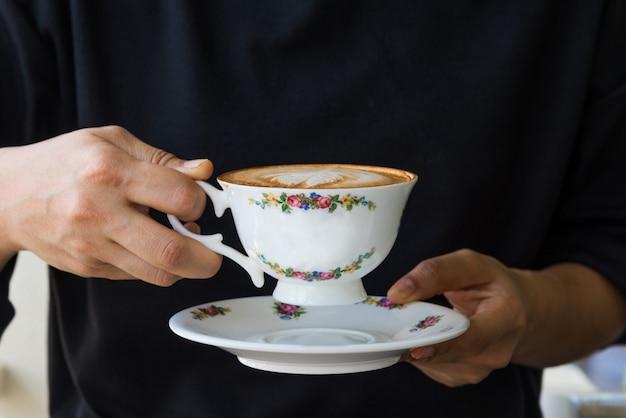 Schließen sie oben von den frauenhänden, die weinlesetasse kaffee halten