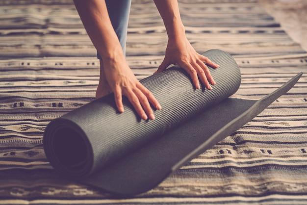 Schließen sie oben von den frauenhänden, die yogamatte vom boden nach der aktiven täglichen übungssitzung des fitness-innentrainings abnehmen