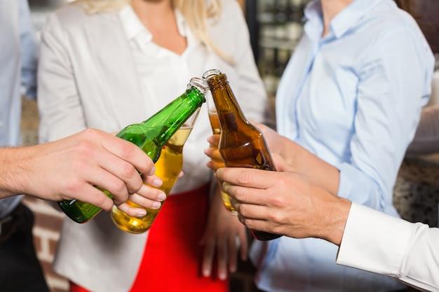 Schließen sie oben von den freunden, die mit flaschen bier rösten