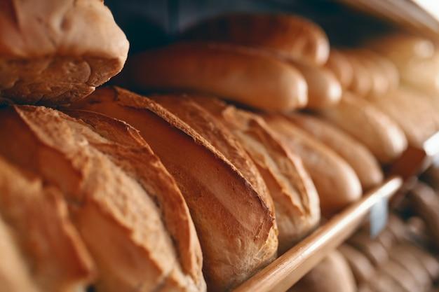 Schließen sie oben von den frischen köstlichen brotlaibs in reihe auf den regalen, die zum verkauf bereit sind. bäckerei interieur.