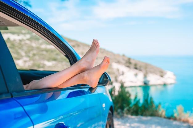 Schließen sie oben von den füßen des kleinen mädchens, die vom autofensterhintergrundmeer darstellen