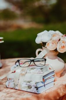 Schließen sie oben von den gläsern auf vintagen notizbüchern auf tisch nahe vase mit blumen. retro-stil in rosatönen. hochzeitstag konzept.