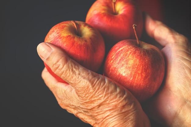 Schließen sie oben von den händen der älteren frau, die bündel organische rote köstliche äpfel halten.