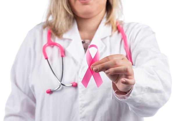 Schließen sie oben von den händen der ärztin mit rosa stethoskop, das brustkrebs rosa band hält