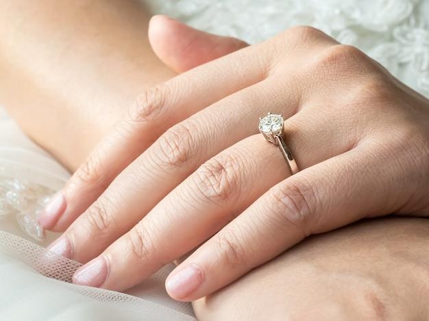 Schließen sie oben von den händen der asiatischen frau den ring mit diamanten zeigend