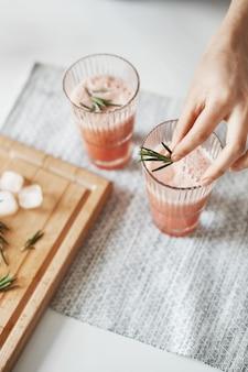 Schließen sie oben von den händen der frau, die gesunden smoothie der grapefruitentgiftung mit rosmarin verzieren.
