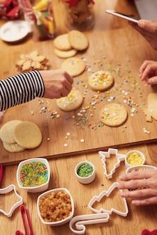 Schließen sie oben von den händen der frau, die kekse für weihnachten verzieren