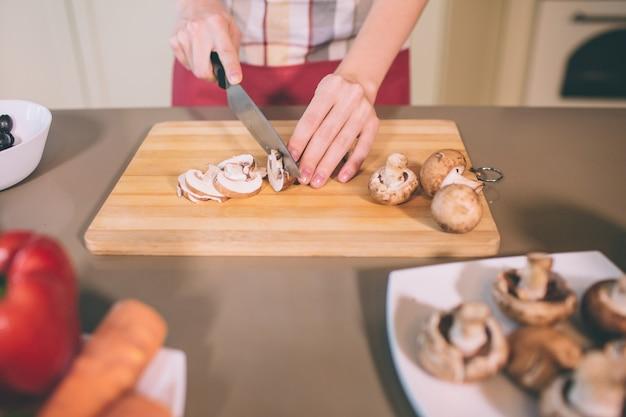 Schließen sie oben von den händen der frau, die pilz in stücke schneiden. sie macht das vorsichtig. mädchen benutzt messer. es gibt teller mit festen pilzen und anderem gemüse.