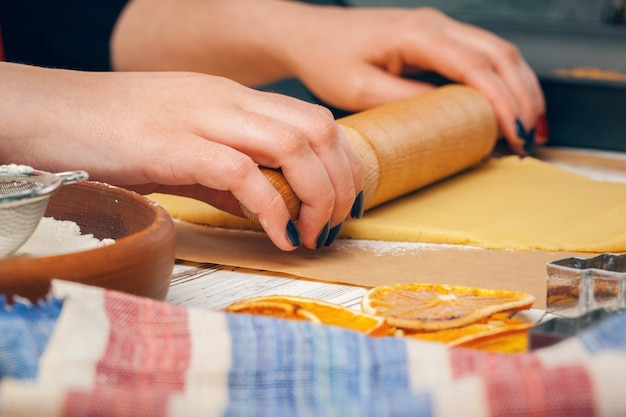 Schließen sie oben von den händen der frau, die teig für kekse vorbereiten