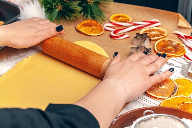 Schließen sie oben von den händen der frau, die teig für plätzchen zubereiten