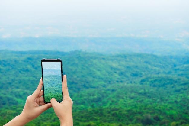 Schließen sie oben von den händen der frauen, die den smartphone halten, der foto bei phuhinrongkla macht, um auf internetsocial media zu teilen