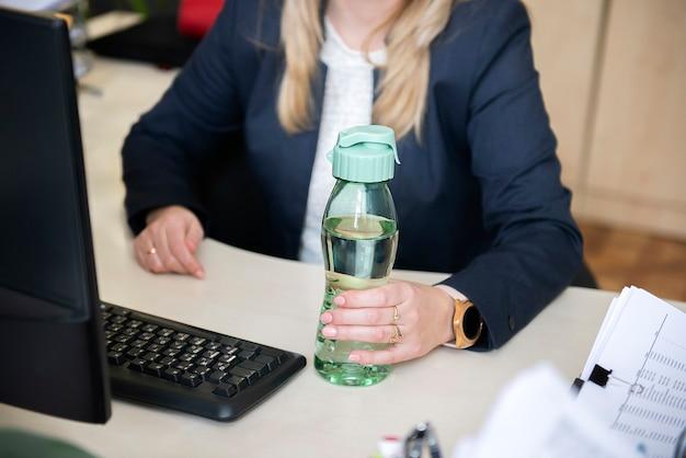 Schließen sie oben von den händen der geschäftsfrau, die mineralwasser der plastikflasche auf einem schreibtisch im büro halten