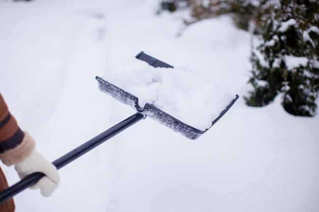 Schließen sie oben von den händen der jungen frau, die schnee vom weg schaufeln