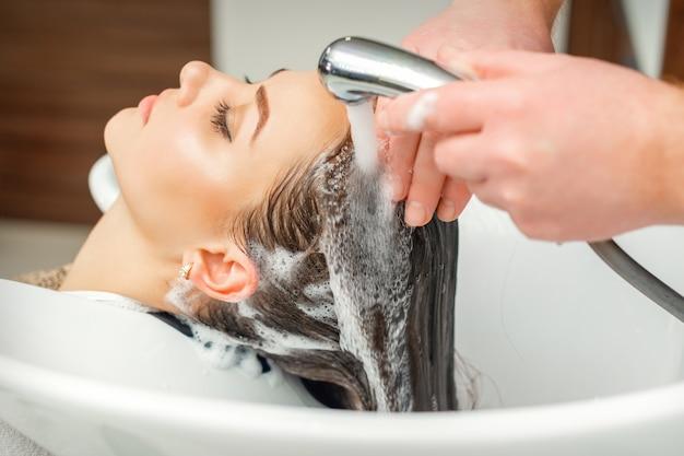 Schließen sie oben von den händen des friseurs, der haar der frau im waschbecken am schönheitssalon wäscht