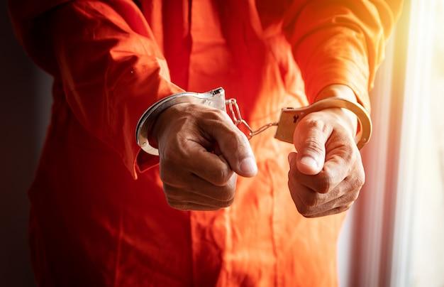 Schließen sie oben von den händen des gefangenen mit den handschellen im orange overall am gefängnis