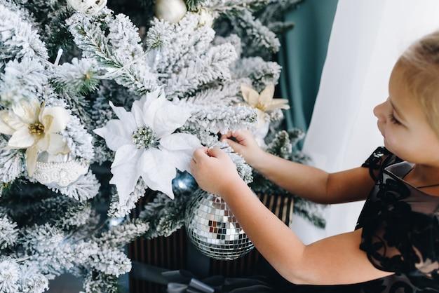 Schließen sie oben von den händen des kleinen kaukasischen mädchens, die verzierungen auf weihnachtsbaum setzen, gestylt in blau und grau
