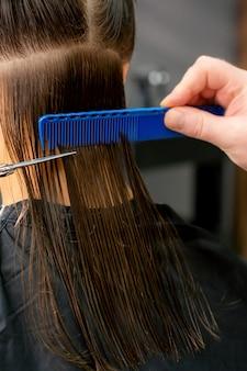 Schließen sie oben von den händen des männlichen friseurs, der langes haar der jungen frau schneidet, die schere und kamm am salon hält. rückansicht