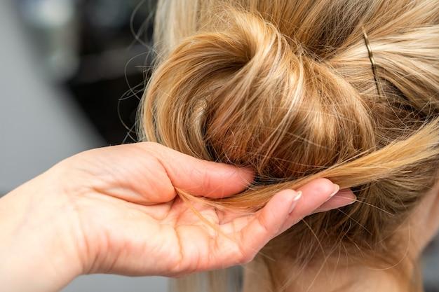 Schließen sie oben von den händen des weiblichen friseurs, der haar einer blonden frau in einem friseursalon stylt