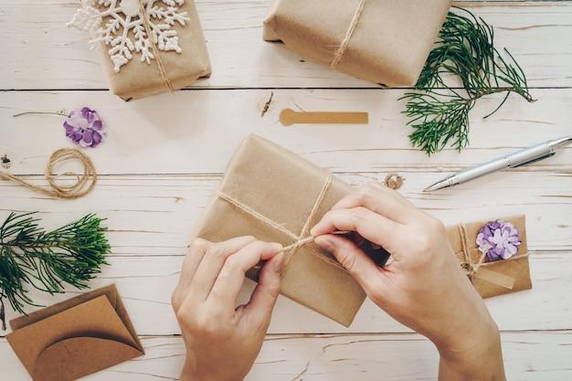 Schließen sie oben von den händen, die geschenkbox auf holztisch mit weihnachtsdekoration einwickeln halten.