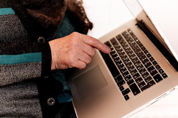 Schließen sie oben von den händen einer älteren großmutter, die auf einem laptop tippt