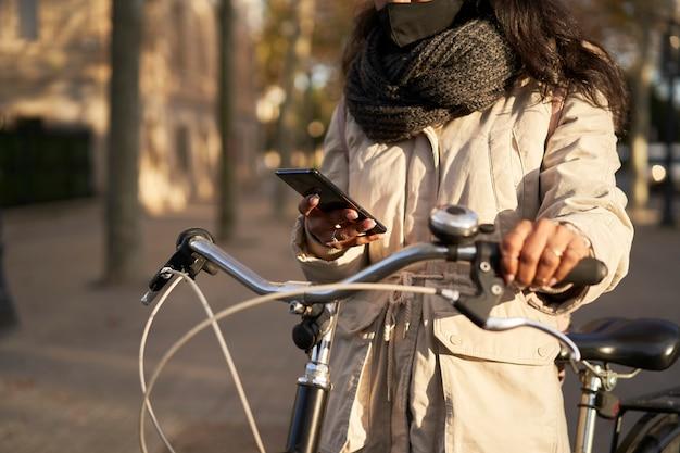 Schließen sie oben von den händen einer jungen nicht wiedererkennbaren frau auf ihrem fahrrad unter verwendung ihres smartphones. sie trägt winterkleidung und ist in einer stadt mit herbstwetter.