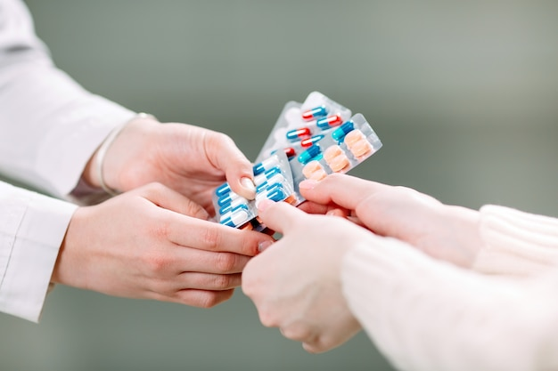 Schließen sie oben von den händen eines mädchens, die pillen in einer apotheke kaufen.