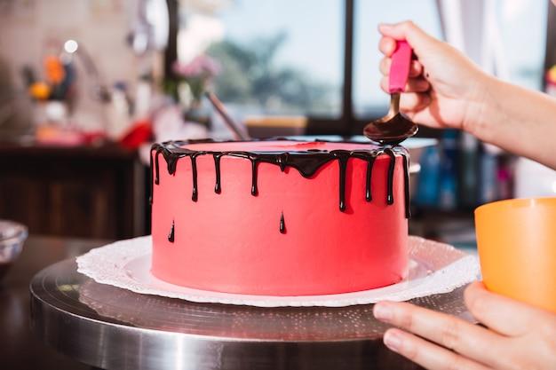 Schließen sie oben von den händen eines weiblichen kochs mit süßwarenbeutel, der flüssige schokolade auf kuchen drückt.