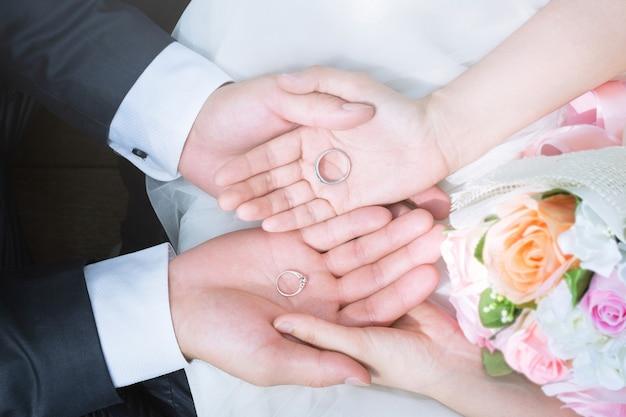 Schließen sie oben von den händen von braut und bräutigam mit eheringen auf ihren handflächen neben einem blumenstrauß