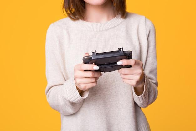 Schließen sie oben von den handfrauen, die videospiele und weibliches halten des joysticks über gelbem lokalisiertem hintergrund spielen