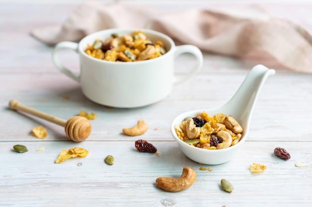 Schließen sie oben von den hausgemachten honig-karamell-cornflakes in der weißen schüssel mit cashewnuss, kürbiskernen und getrockneten rosinen auf weißem holz