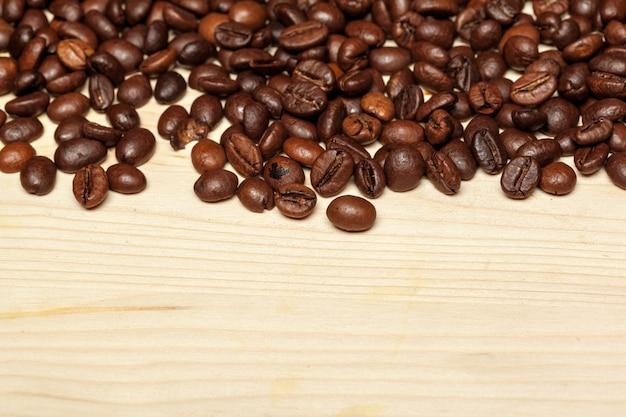 Schließen sie oben von den kaffeebohnen auf einem hölzernen hintergrund